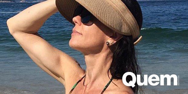 Flavia Monteiro. Foto do site da Quem Acontece que mostra Aos 45 anos, Flavia Monteiro exibe boa forma de biquíni em dia de praia