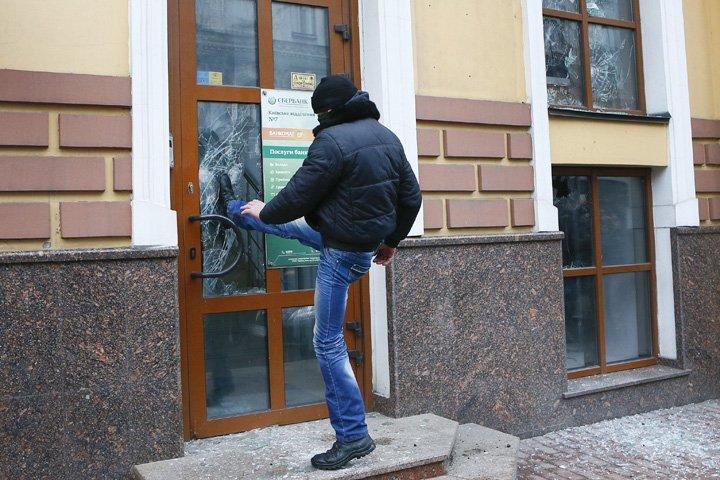 @BroadcastImagem: Ativista ucraniano da extrema-direita depreda fachada de banco russo durante ato em Kiev. Efrem Lukatsky/AP