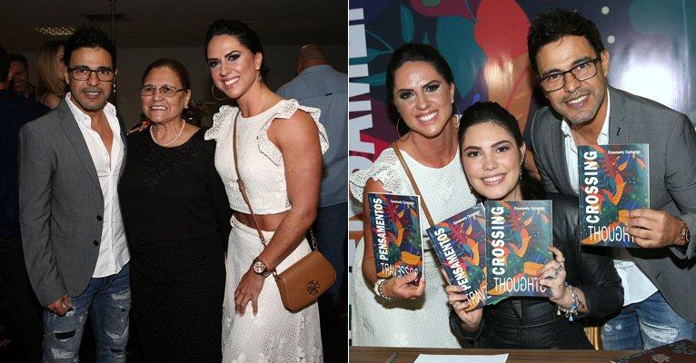 Graciele Lacerda. Foto do site da Caras Brasil que mostra Zezé di Camargo e Graciele Lacerda posam com a mãe do cantor em lançamento de livro