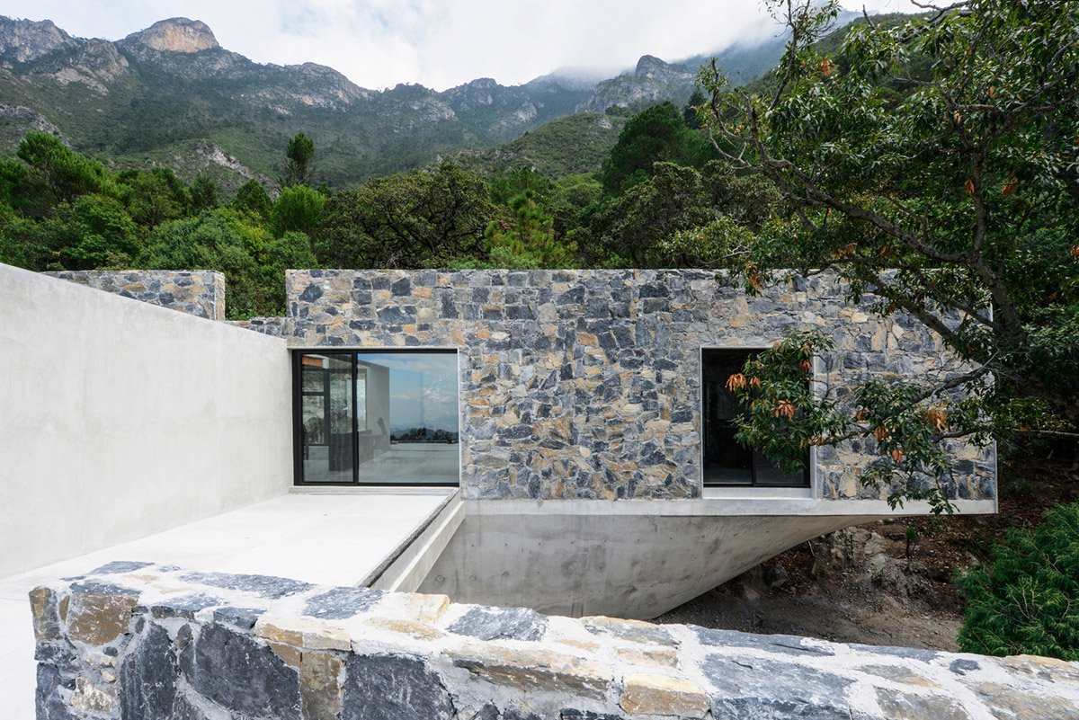 P+0 Arquitectura designs residence mixed with concrete and stone volumes on a complex terrain