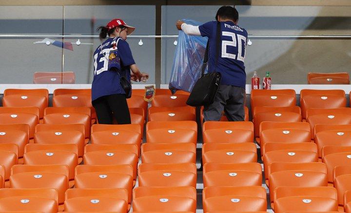 @BroadcastImagem: Torcedores do Japão recolhem lixo das arquibancadas após a partida contra o Senegal. Eugene Hoshiko/AP