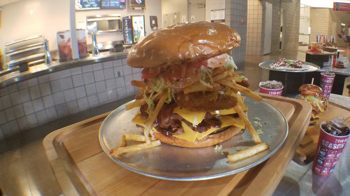 UP FOR THE CHALLENGE? The Arizona Cardinals have introduced the hefty $75 Gridiron Burger. It includes 5 patties, 5 hot dogs, 5 bratwurst, 8 slices of bacon, 20 slices of American cheese, 12 ounces of fries and 8 chicken tenders. Eat it in an hour to win a Cardinals jersey. 😱 https://t.co/ELG2NvIhwR