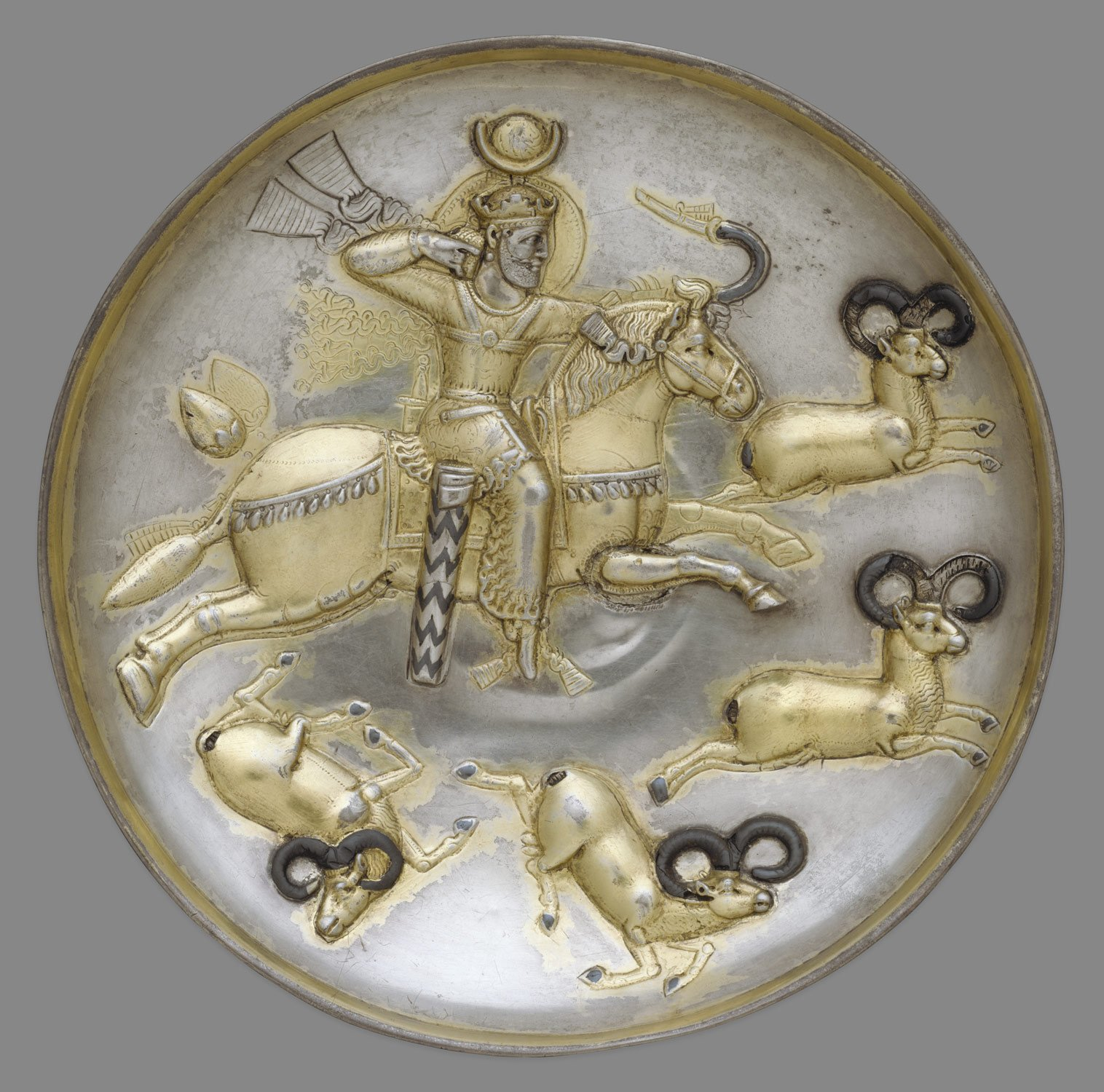 Plate with king hunting rams, #Iran, #Sasanian, mid-5th–mid-6th C., Silver and mercury gilding. The Sasanian king on this plate has various royal attributes: a crown and fillet, covered globe, nimbus with beaded border, and beaded chest halter with fluttering ribbons. (metmuseum) https://t.co/xG72xmp8NS