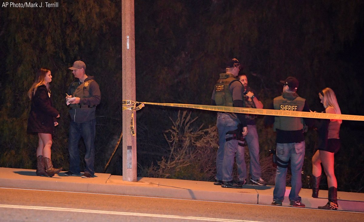 Sheriff's deputies speak to potential witnesses as they stand near the scene in Thousand Oaks, Calif., where a gunman opened fire inside a country dance bar.