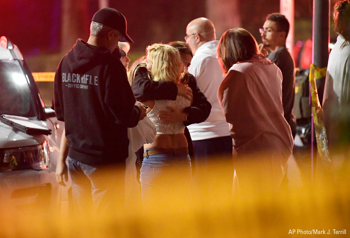 """People comfort each other as they stand near the scene in Thousand Oaks, Calif. where a gunman opened fire during a """"college country night"""" at a bar."""