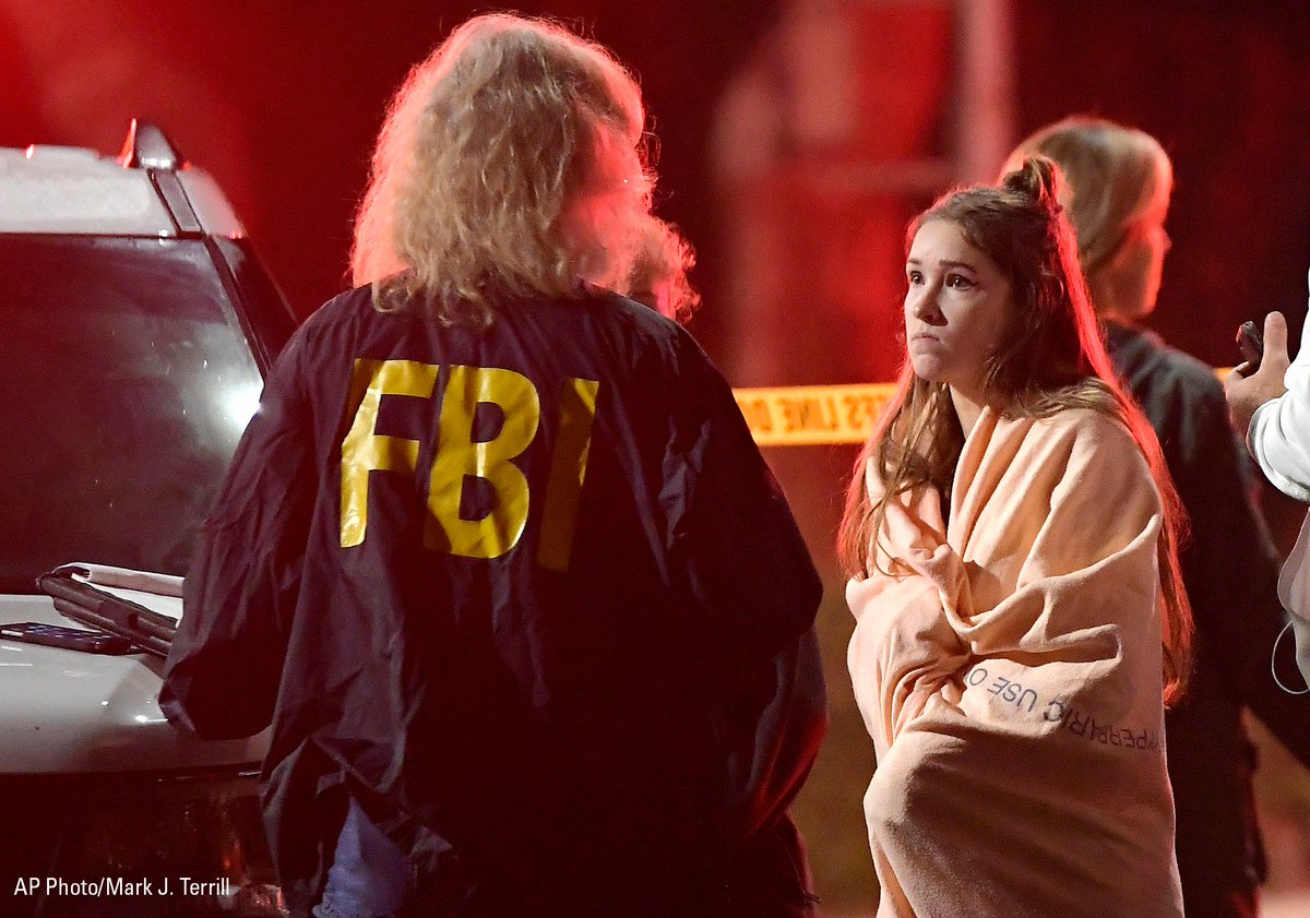 """An FBI agent talks to a potential witness as they stand near the scene in Thousand Oaks, Calif. where a gunman opened fire during a """"college country night"""" at a bar."""