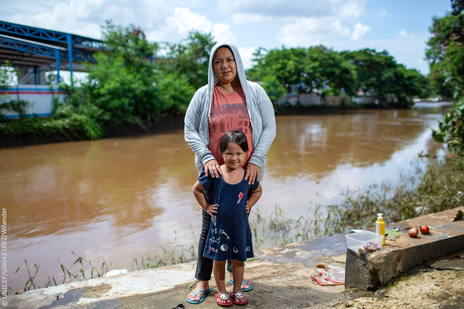 Cello, 3, and her mother Selly stand in front of an overflowing river that inundated their home in Indonesia after days of heavy rain.  Without action now, the climate crisis will worsen the inequalities that many children already face. https://t.co/LBfEojeJ2a