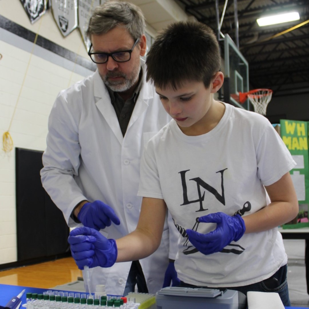 Tyler Goeschel, assistant manager for Little Blue NRD, observes Lawrence-Nelson student, Caden, as he tests some water for nitrates during the Lawrence-Nelson Science Fair yesterday in Nelson. #sciencefair #NRD #nitrate #water
