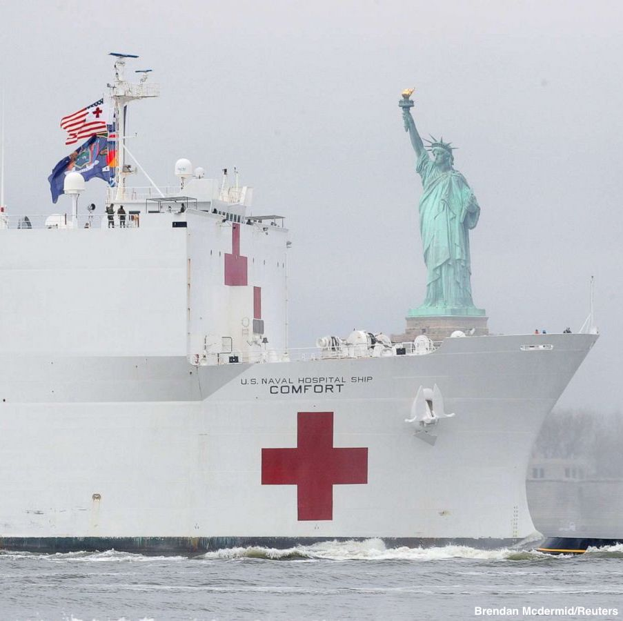 The USNS Comfort, a Navy hospital ship on loan to the coronavirus fight, passes by the Statue of Liberty.
