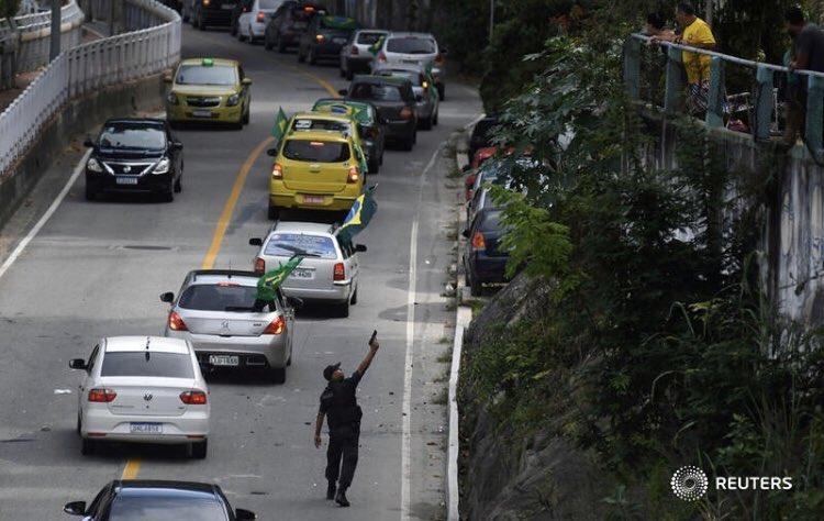 Policial militar aponta arma para moradores do Vidigal que jogavam ovos na carreata pró-Bolsonaro.  Foto de Lucas Landau para a Reuters.
