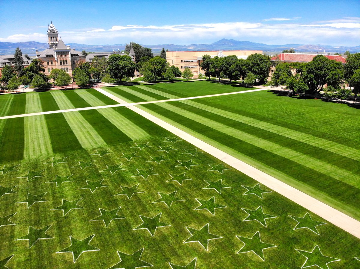 Landscapers at USU mow an American Flag into the grass on the Quad.