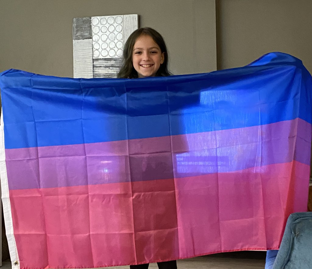 my little sister came out as bisexual so i bought her a flag and look how happy she looks, my heart 🥺