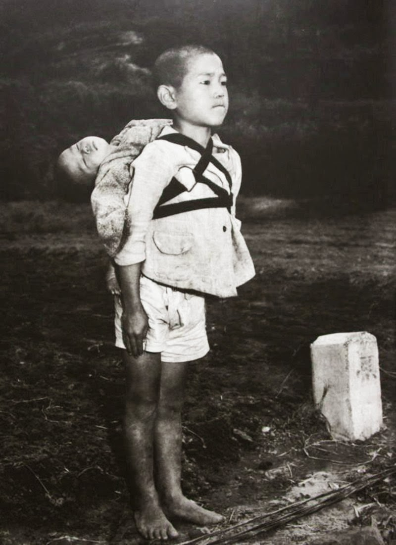 A Japanese boy standing at attention after having brought his dead younger brother to a cremation pyre, 1945, Nagasaki.   Photo taken by Joe O'Donnell.
