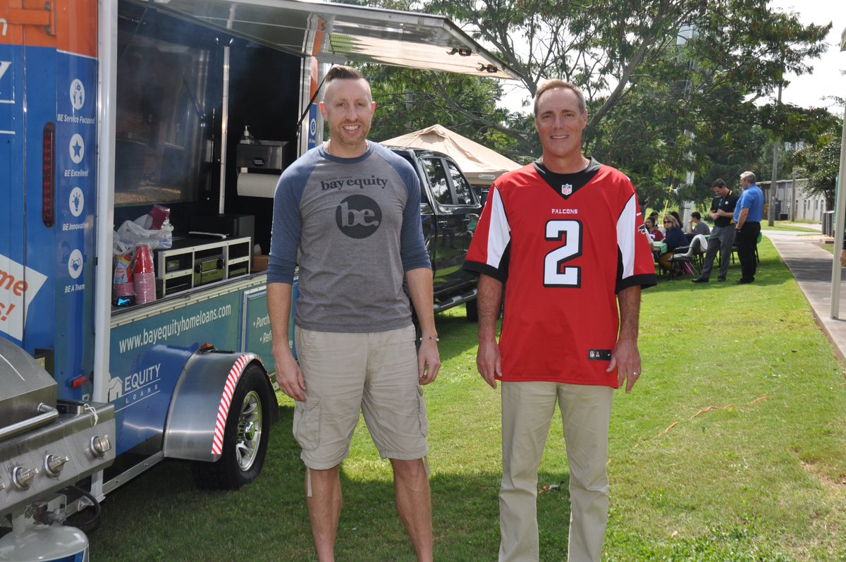 JOB WELL DONE: Jay White with Bay Equity Home Loans heard about our successful school restart and treated all available staff members at Central Office to a Tailgate Lunch! Thanks, Jay! Here he is with our football-loving superintendent!