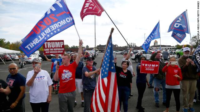 "As Biden spoke at a drive-in rally in Bucks County, Pennsylvania, a group of what appeared to be Trump supporters nearby honked horns, waved flags and shouted ""four more years"""