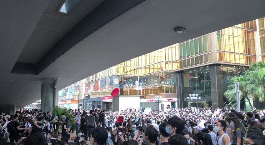 Umbrellas rain down from the overpass above Harcourt Road after police unfurl a red warning flag. During the 2014 Umbrella Movement, they were used to protect against pepper spray. Full coverage: http://bit.ly/extraditionhk   #NoToChinaExtradition