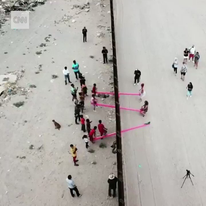 Artists installed these neon pink seesaws on both sides of the border fence so kids in the US and Mexico can play together . Politicians divide, children unite!