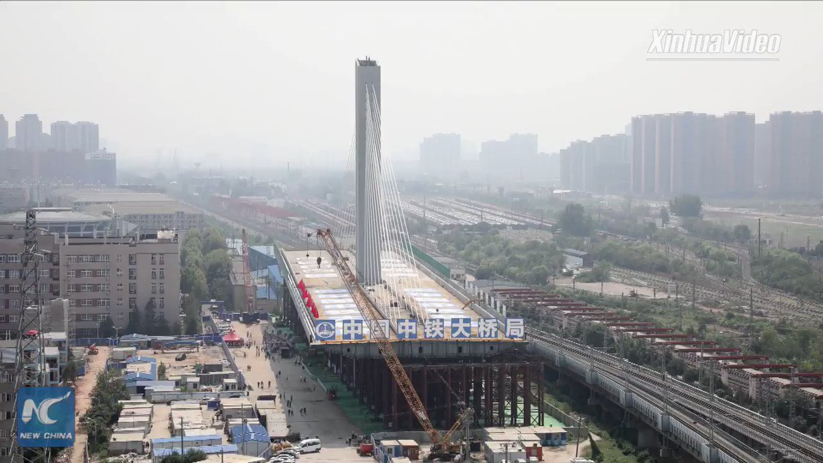 A 36,000-tonne cable-stayed bridge rotates to its position above 11 railway lines in Wuhan, central China