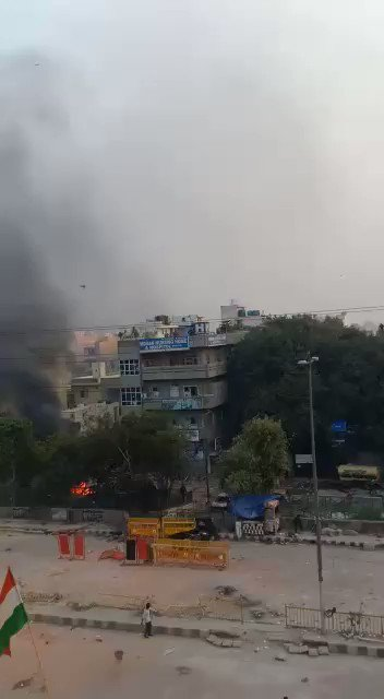 This is the most shocking video from #DelhiRiot2020 Caught on mobile camera, wearing helmet, firing bullets from top of a hospital building?Where is AajTak, Times Now team?