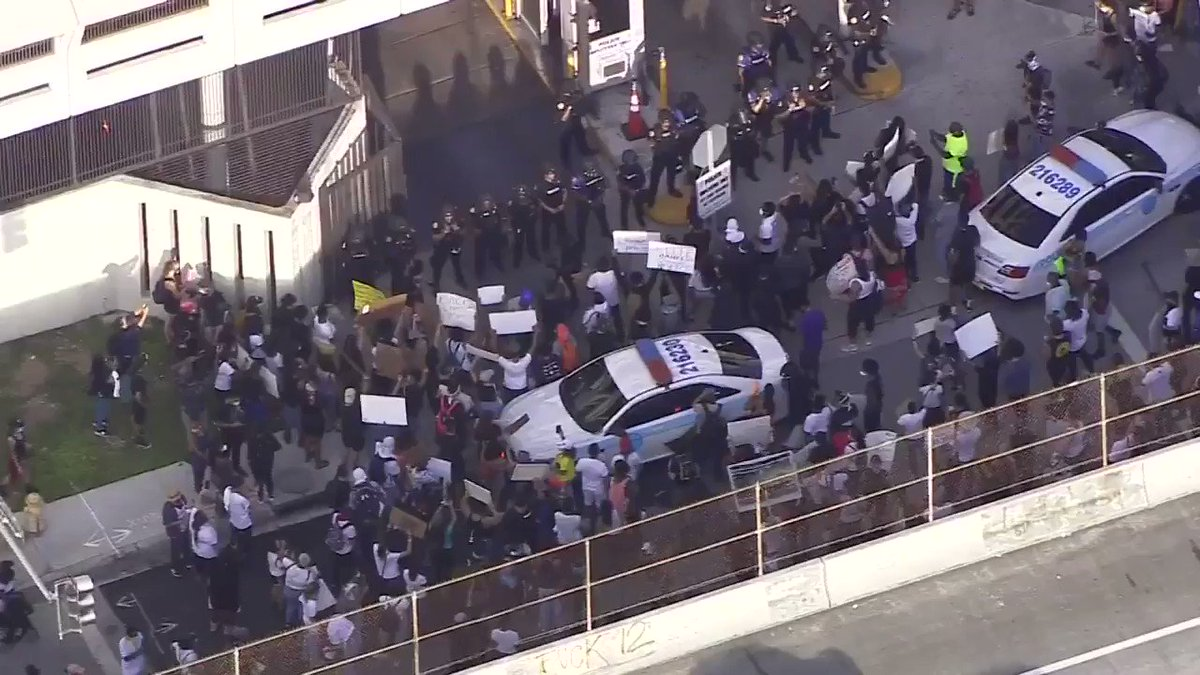 Dozens of protestors are currently standing outside a City of Miami Police Department: