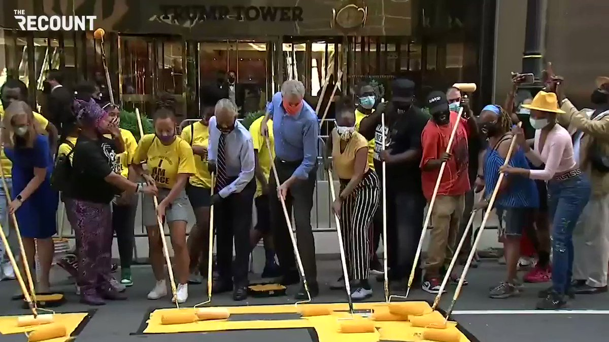 Members of the exonerated Central Park Five help paint #BlackLivesMatter on the street in front of Trump Tower on New York's Fifth Avenue.