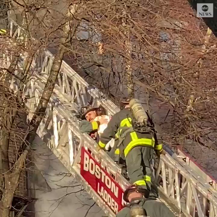 TO THE RESCUE: Boston firefighters carry a small child out of a Two Alarm fire at a four-story apartment building. A woman and two children were saved from the blaze, and no injuries were reported.