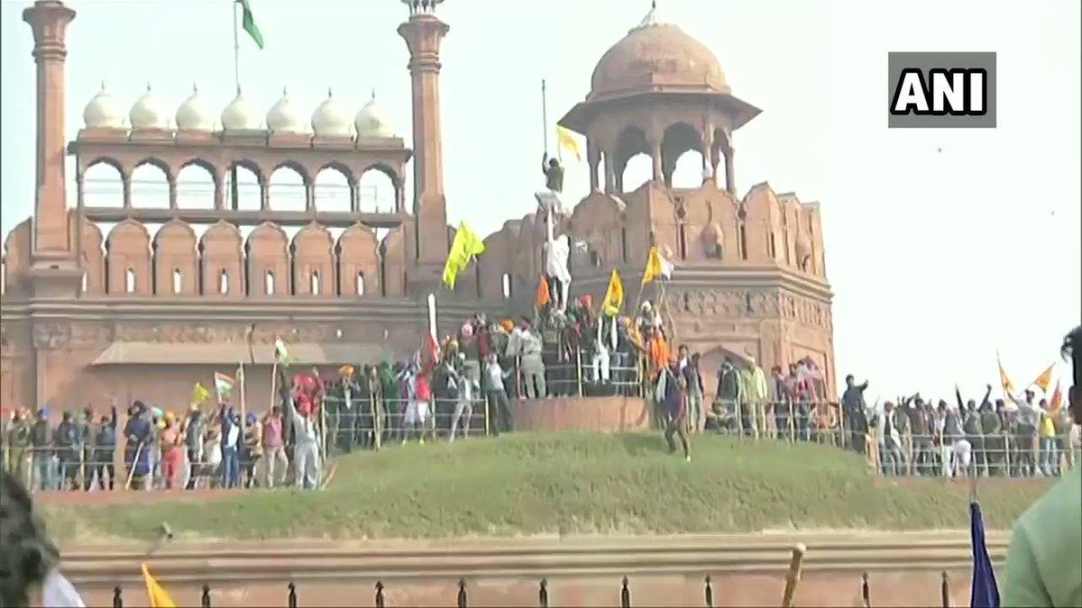 #WATCH A protestor hoists a flag from the ramparts of the Red Fort in Delhi  #FarmLaws #RepublicDay