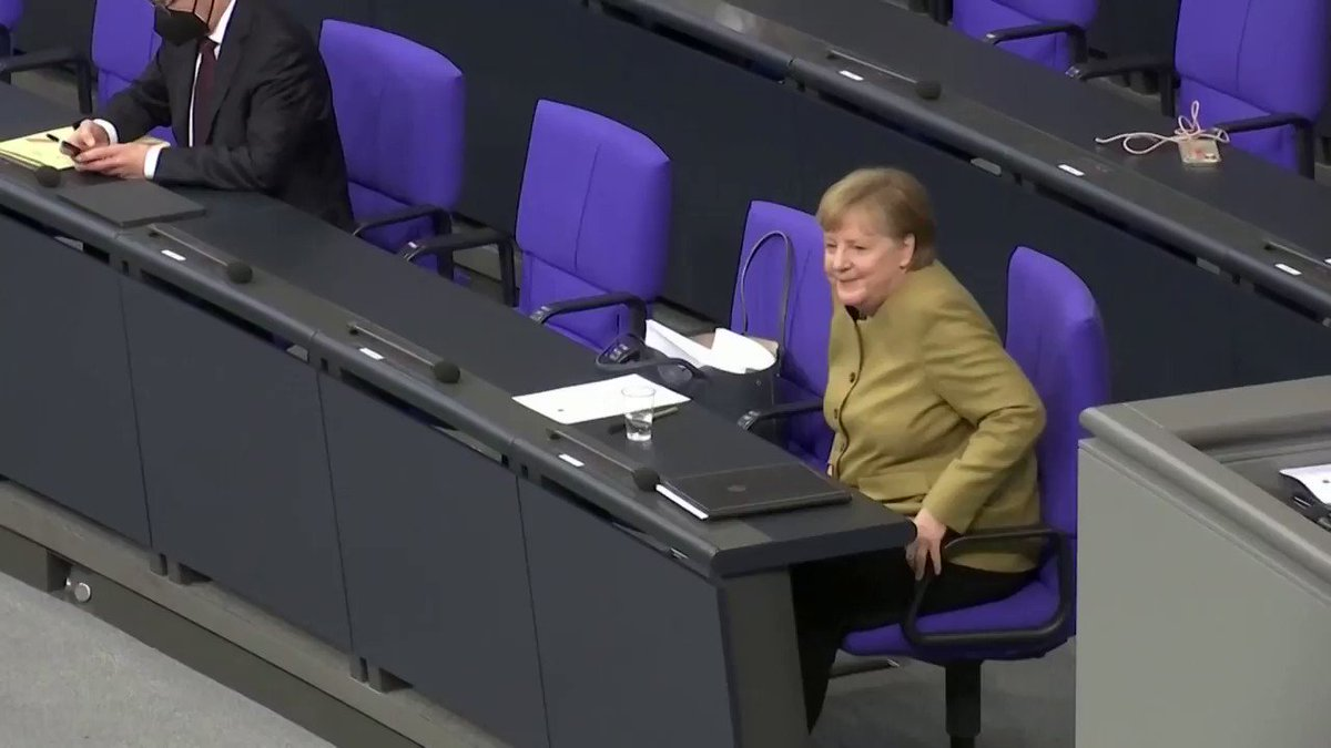 German Chancellor Angela Merkel panics after forgetting her face mask on the lectern during a speech in parliament