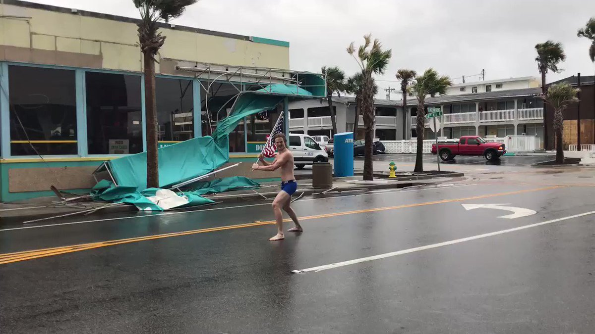 Me: what are you doing? There is flying debris Half naked man: I went viral a few years ago doing this. #FlorenceHurricane2018 #viral #americanflag