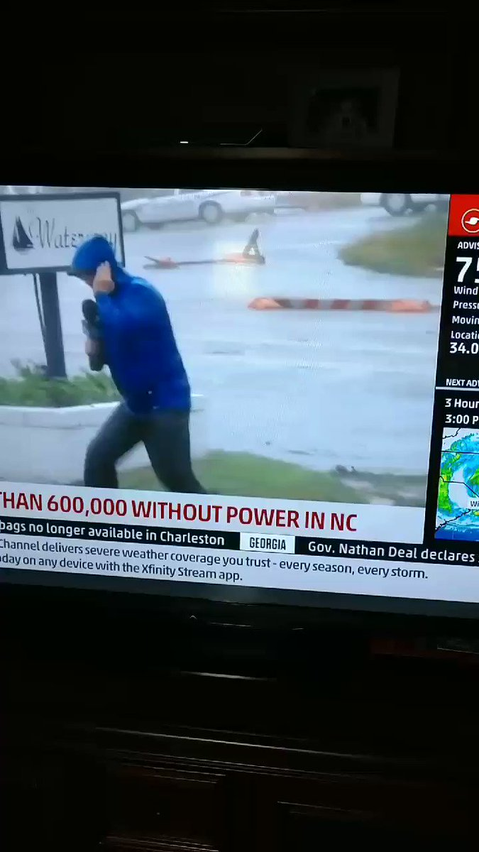 Weatherman dramatically braces for Hurricane Florence while 2 guys casually stroll by