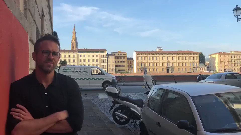 Chill Ryan Reynolds chats from Michael Bay set while cars flip and crash behind him