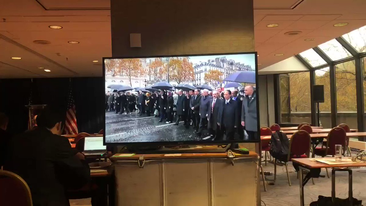 World leaders are walking shoulder to shoulder along the Champs Elysses but Trump arrived separately and isn't participating in this.