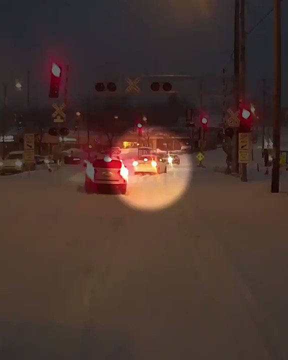 City bus driver stops to help a car stuck in snow on train tracks