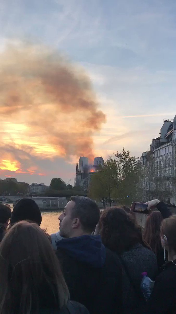 #NotreDame in flames. Silent crowds look on, many in tears, as the fire is still strong.