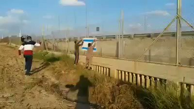 Palestinians at the security fence today set Israeli flag on fire. #Gaza #Israel