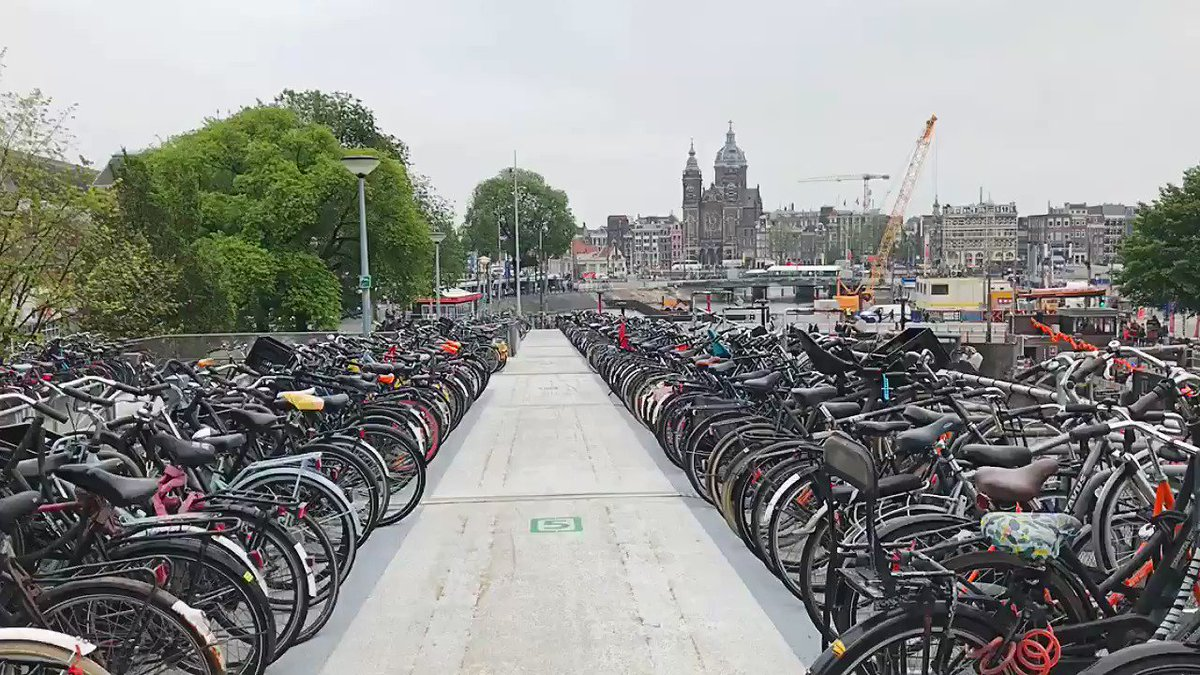 """The """"fietsflat"""" was first built in 2003, as a temporary means to store bicycles while Amsterdam Central Station was undergoing renovations.  Now, this permanent 100-metre-long floating structure holds 2,500 bikes, and is the single most photographed attraction in the entire city."""