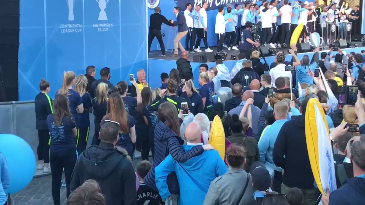 If this is a celebration of ALL Manchester City's wins / trophies / successes this season...  Why are the female players - who did the cup double - not on the stage with the men right now...?   That's them watching from the side and filming on their phones...?
