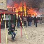背後で大火事。にもかかわらずブランコで遊ぶ少年