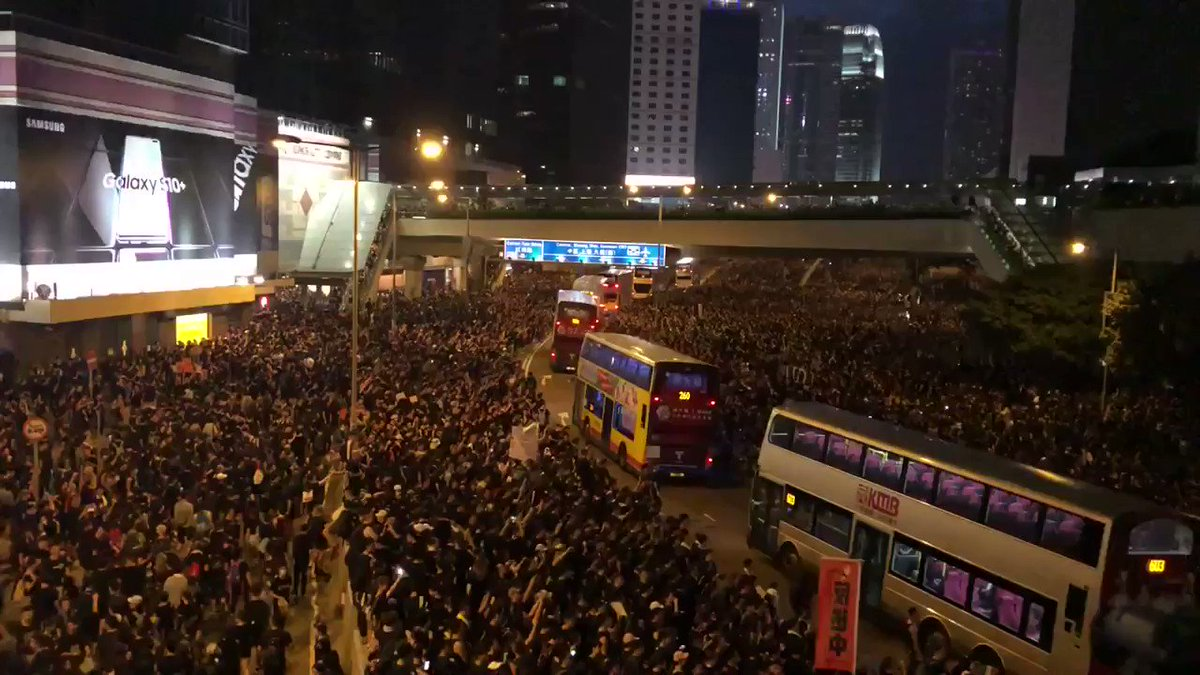 Amidst cheers, the crowd on Harcourt Road parts to allow buses through and then regathers behind them.