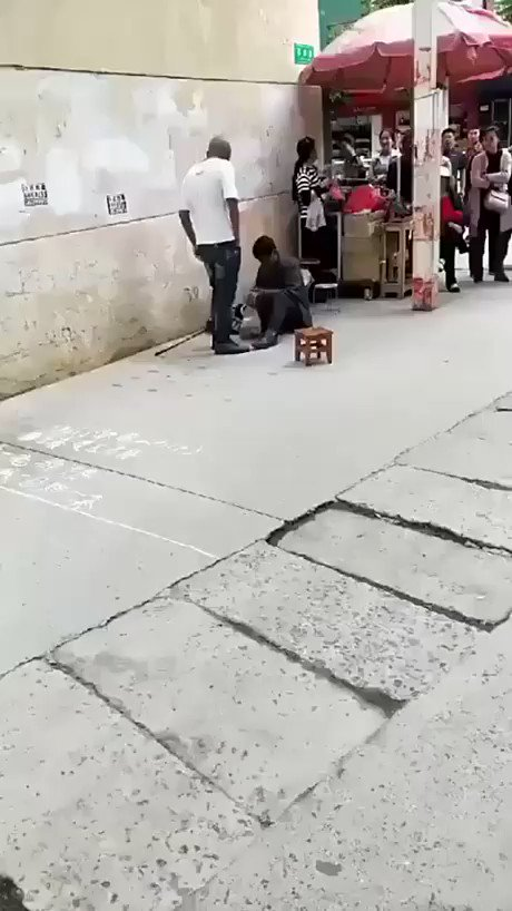 Man is harassing a beggar on the street, gets some karma kicked in his body.
