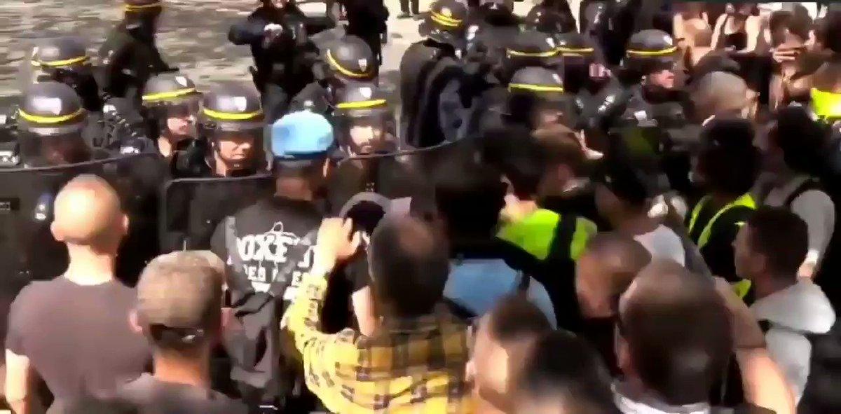 Le monde a lenvers ! Les #GiletsJaunes tentent de calmer la police qui frappe sans raison des manifestants. La police a attrapé des gj pour les empêcher dentrer dans un magasin pour acheter de leau... On en est là. #Acte39