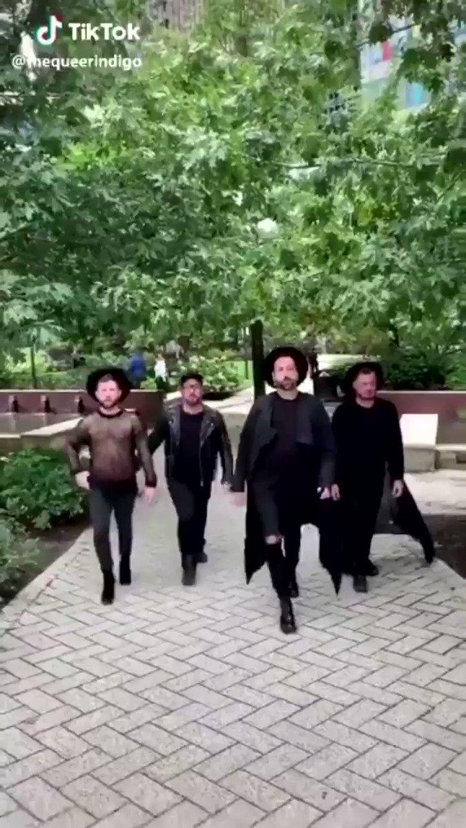 four people wearing black and walking