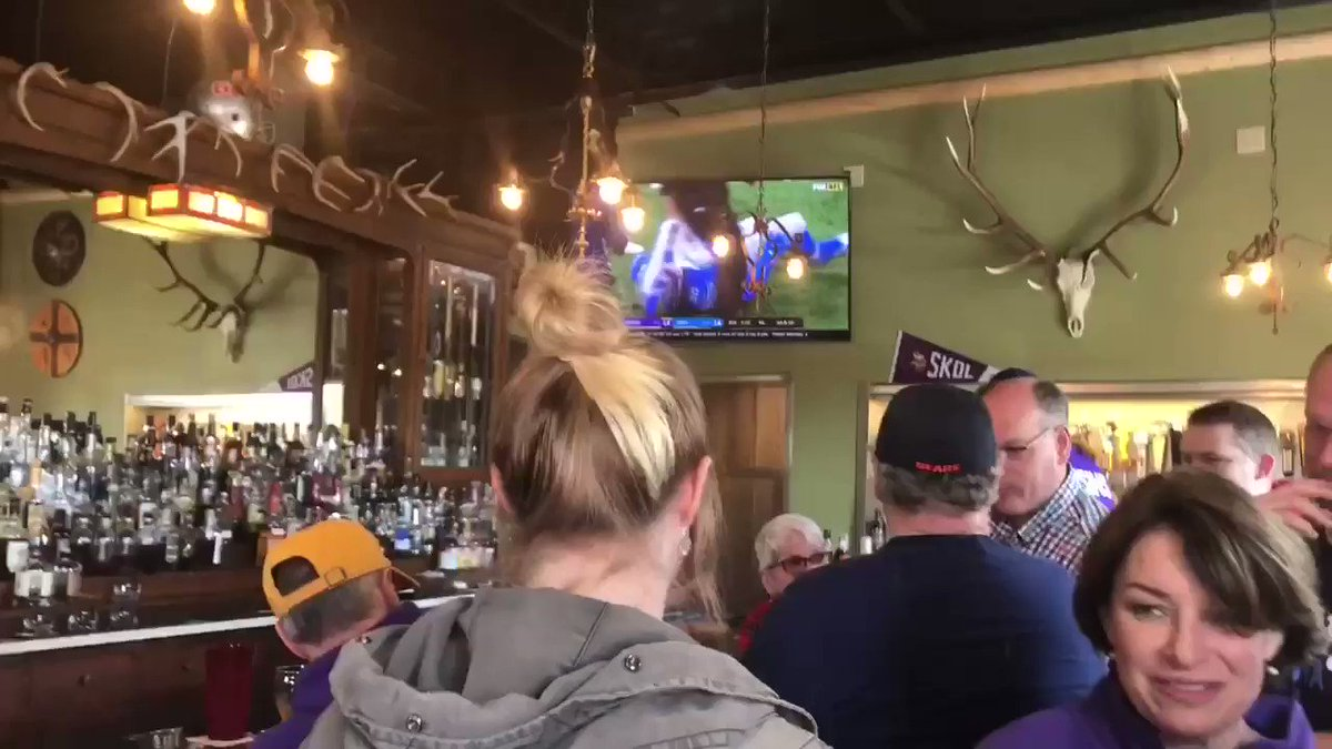 .@amyklobuchar gets a proper Vikings welcome at Skol, a Minnesota Vikings bar in Des Moines. Grabs a purple beer on her way in