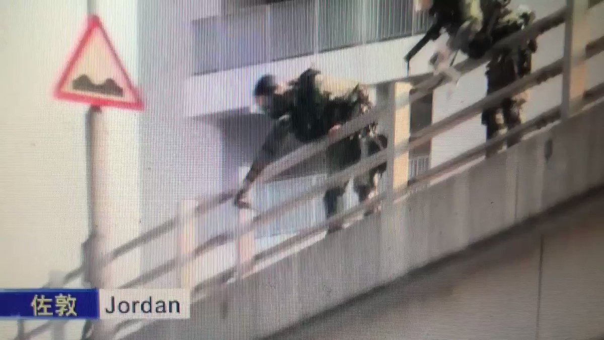 Riot police officers are seen firing rounds and pepper spray at protesters from an overpass in Jordan #polyu