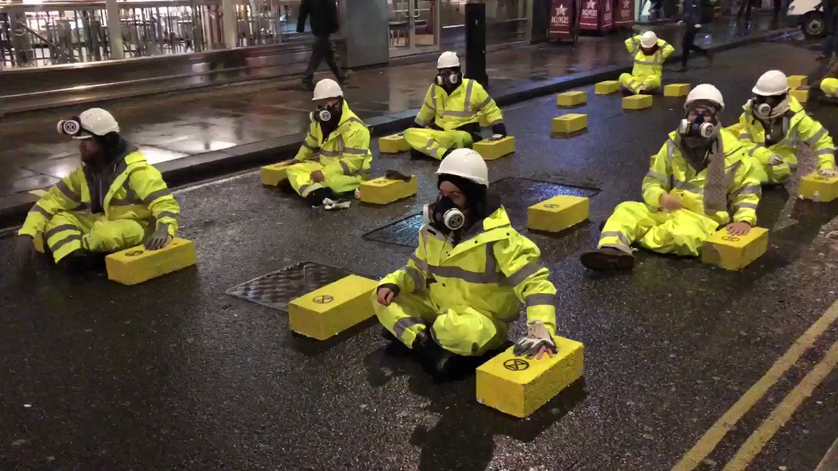 "Extinction Rebellion have glued themselves to blocks of concrete stuck to road outside Leicester Square tube station. Today's campaign is all about air pollution. Their sign reads ""Air Pollution Kills 25 Londoners Each Day."" @LBC"