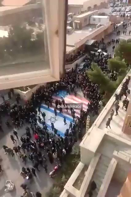 Student protesters at Tehran's Beheshti University take pains to avoid trampling on US and Israeli flags painted on entrance walkway