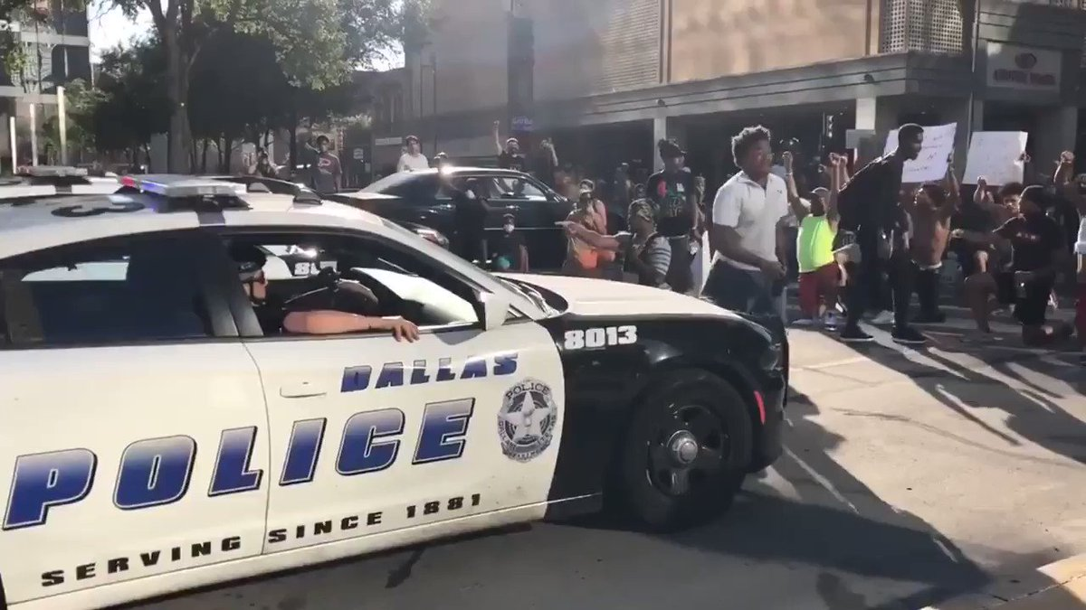 Our officers join the peaceful protesters and take a knee. @CityOfDallas @ChiefHallDPD