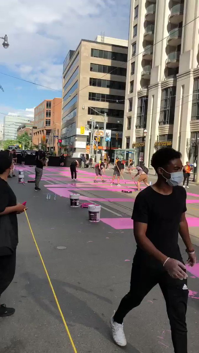 """Black Lives Matter day of action on College Street in Toronto right now. #BlackLivesMatter @BLM_TO members are painting the message """"Defund the Police"""" in bright pink paint outside of Toronto Police Headquarters. #CBC #torontopolice #BlackLivesMatter"""