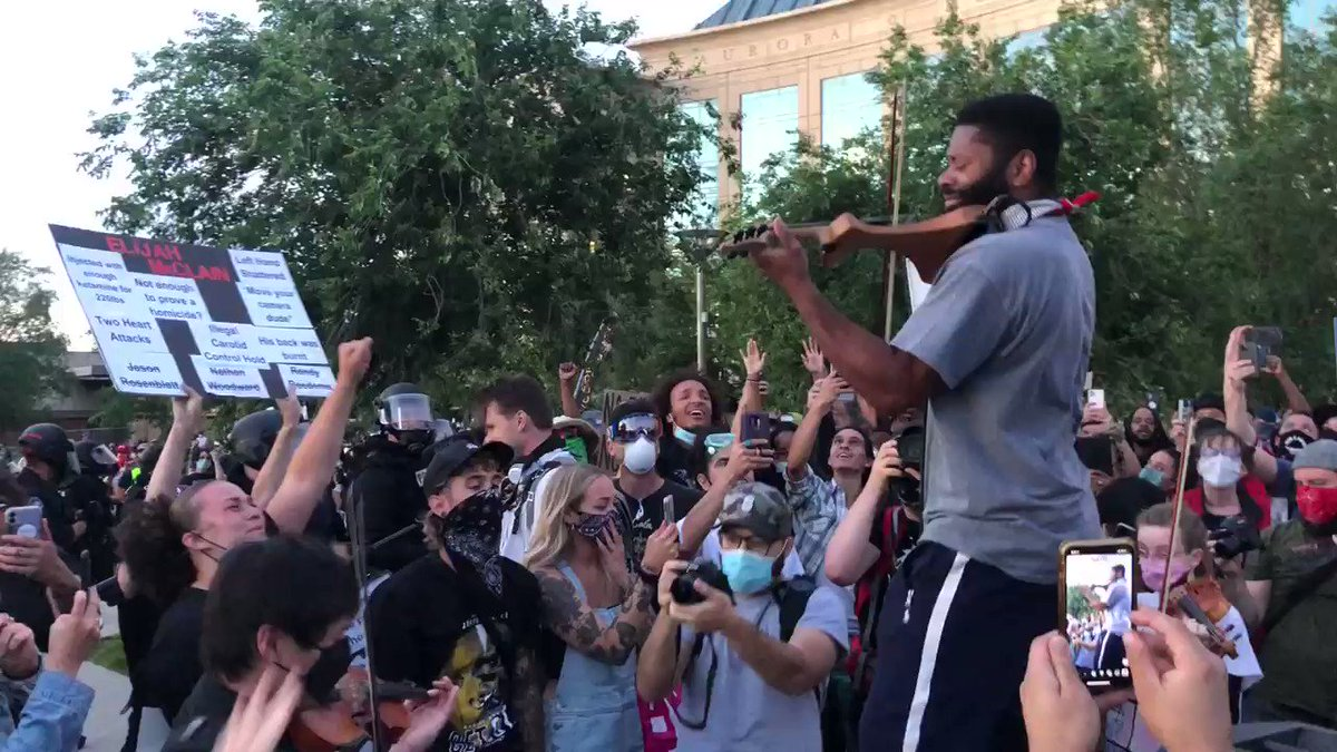 """As Aurora Police in riot gear sweep the protest from the municipal park, this dude fires up his electric violin and literally stopped the police.  Cops 10 feet away. Started with Bruce Hornsby """"The way it is"""" then into this masterpiece! #Auroraprotest #ElijahMclain"""
