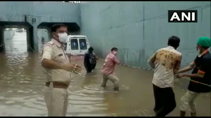 #WATCH Gujarat: An ambulance that was stuck under a waterlogged bridge near Rajkots Gondal earlier today, was pulled to safety by the locals and local administration.